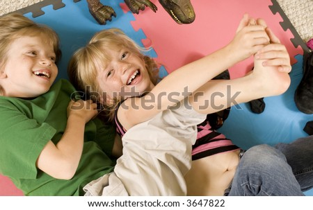 Adorable twins tickling on the playroom floor. - stock photo