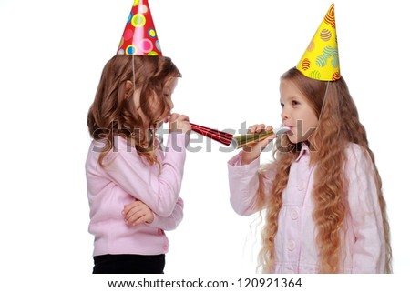 Adorable two friends with party colorful hats and colorful toy horns on Holiday theme