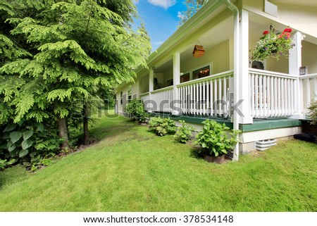 Adorable white house with nice front lawn and trees. - stock photo