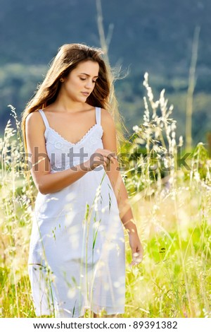adorable woman in a white dress walks serenely though a meadow at sunset