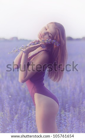 adorable woman in field with flower at summer sunset, portrait series of girls in nature - stock photo