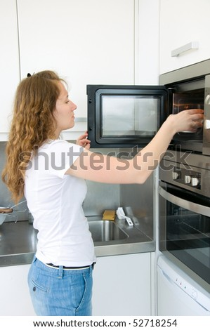 adorable woman is cooking by oven - stock photo
