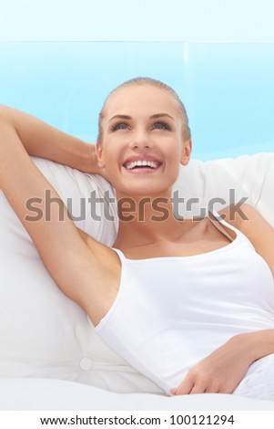 Adorable woman smiling broadly and looking off camera while seated on a white couch - stock photo