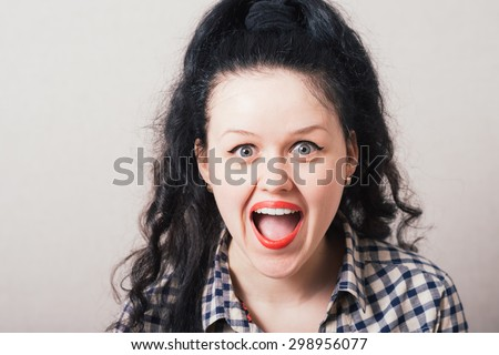 Adorable woman with red lipstick standing in awe looking at camera with mouth and eyes open wide surprised