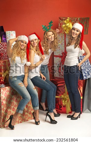 Adorable women sitting next to big gifts - stock photo