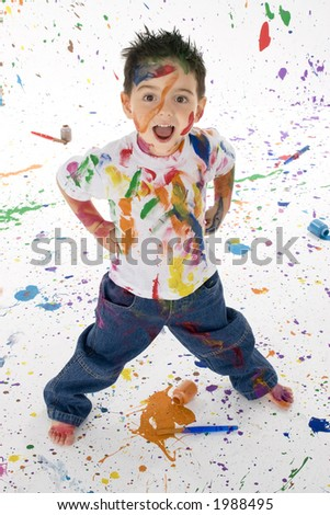 Adorable 3 year old boy child covered in bright paint.  Mess of paint on wall, floor, and child. - stock photo