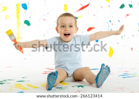 Adorable 3 year old boy child creatively stains on the wall, floor with colourful paint. Mess of paint on wall, floor and everywhere. - stock photo