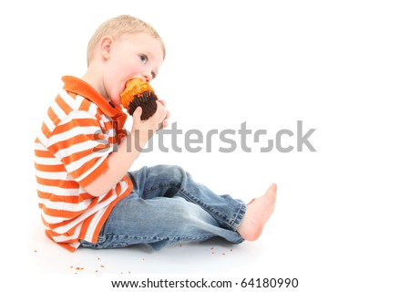 Adorable 2 year old boy eating orange icing cupcake over white background. - stock photo