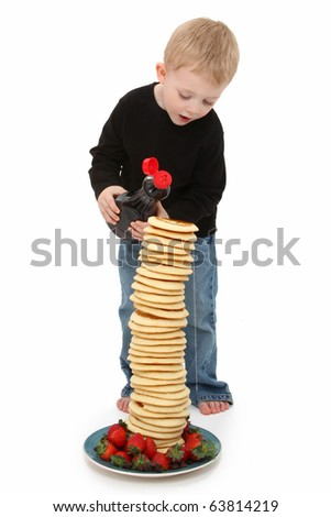 Adorable 2 year old boy pouring syrup on a giant stack of pancakes with strawberries and chocolate over white. - stock photo