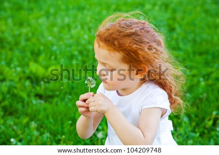 Adorable 3 year old girl blowing dandelion, shallow depth of field, focus on foreground - stock photo