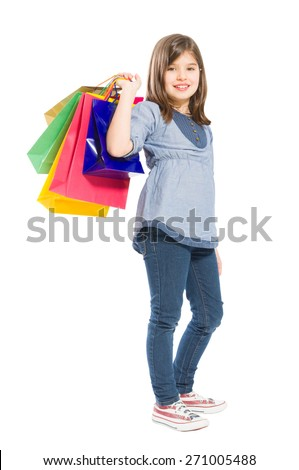 Adorable, young and cute shopping girl carrying shopping bags and smiling - stock photo