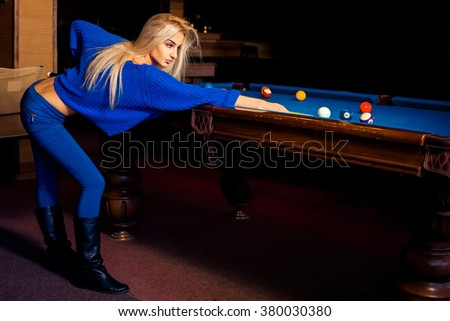 Adorable young beautiful blonde concentrated on pool billiard game. Billiard sport concept. Pool billiard game. American pool billiard. - stock photo