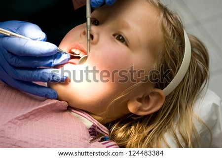 Adorable young blond girl getting her teeth checked at the dentist - stock photo