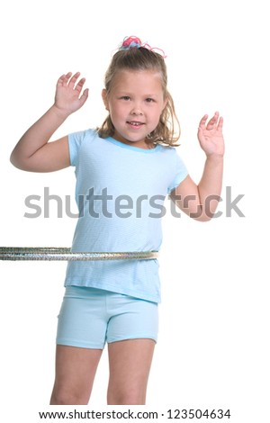 Adorable young blond girl having fun in the studio with a hula hoop - stock photo