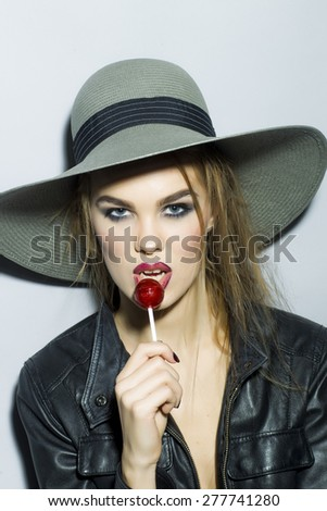 Adorable young blonde girl portrait with bright make up in hat and leather jacket looking forward holding and licking round red sugar candy standing on gray background copyspace, vertical picture - stock photo