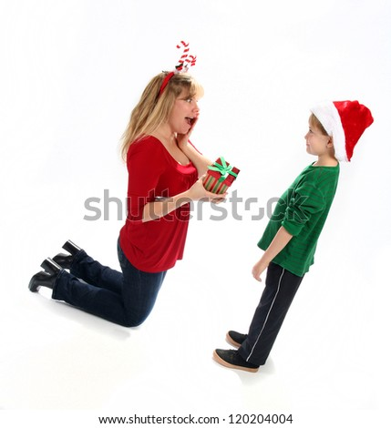 Adorable young boy giving gift to mother for Christmas - stock photo