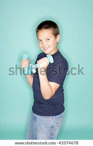 Adorable young boy keeping fit with small weights - stock photo