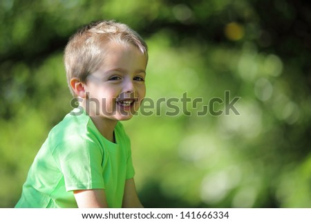 Adorable young boy laughing outdoors in the summer sunshine - stock photo