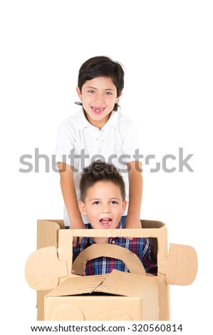 Adorable young boys playing and sitting in a cardboard car isolated over white background. - stock photo
