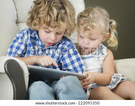 Adorable Young Brother and Sister Using Their Computer Tablet Together. - stock photo