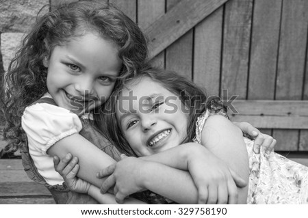 Adorable young brunette girls embracing hugging showing love and friendship, looking into camera black white edition. - stock photo