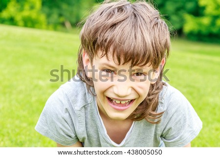 Adorable young child boy in the park. On warm summer day during school holidays. Kid boy dreaming and smiling.