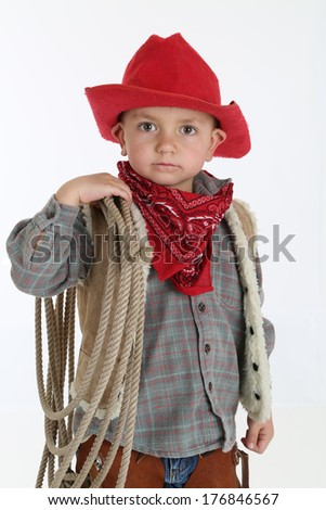 adorable young cowboy wearing hat holding rope