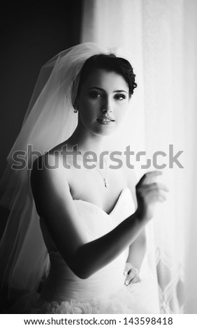 adorable young dark hair bride, getting ready in the morning, black and white portrait - stock photo