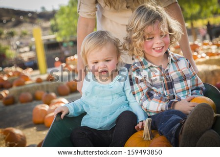 Adorable Young Family Enjoys a Day at the Pumpkin Patch. - stock photo