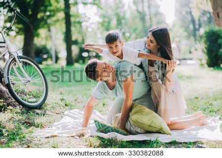 Adorable young family having weekend in a city park - stock photo