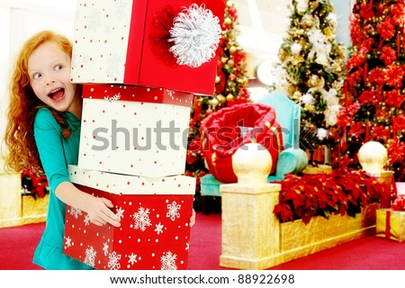 Adorable young girl child holding stack of large Christmas gifts in the mall.  Excited expression.