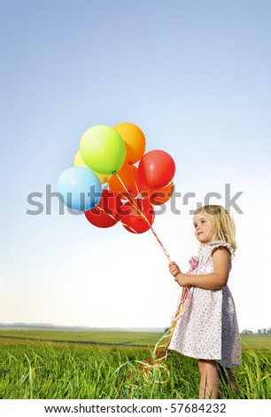 Adorable young girl holds tightly to a large bunch of helium filled balloons - stock photo