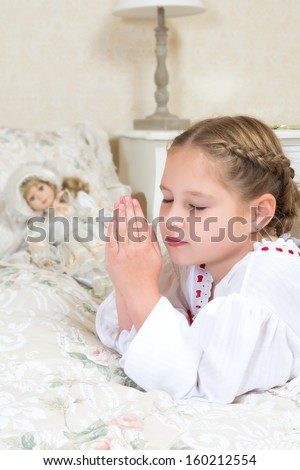 Adorable young girl saying her night time prayers beside her bed