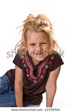 Adorable young girl scrunching her nose for the camera in a brown shirt and jeans on a white background