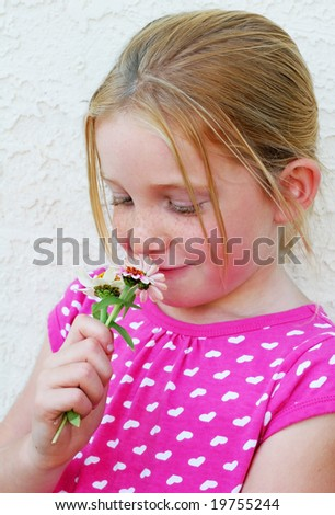 adorable young girl smelling flowers