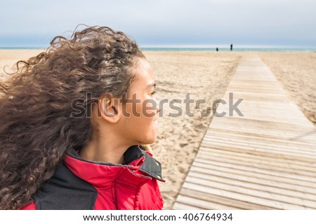 Adorable young girl wearing red coat, walking on beach in Spain in winter. Beautiful brazilian child with long curly hair enjoying wind and sun outside, image for children concept family blog.  - stock photo