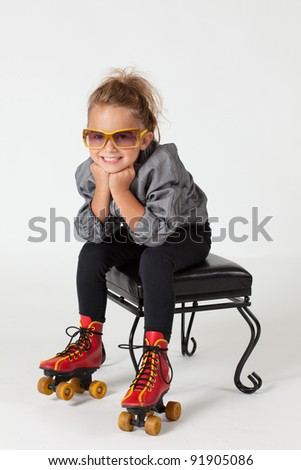 Adorable young girl with roller skates on, sitting on stool on a white background. - stock photo