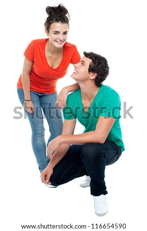 Adorable young guy squatting on floor and looking at his girlfriend - stock photo