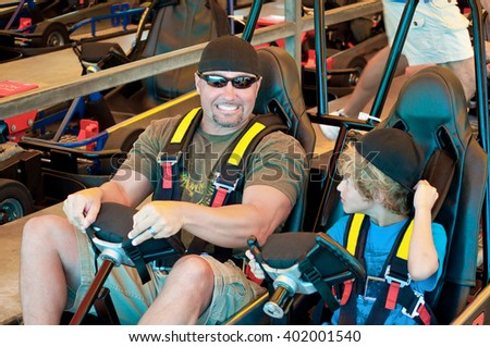 Adorable young kid  with his dad on a go cart at an amusement park. - stock photo