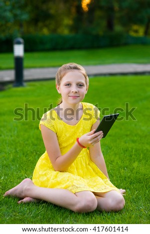 Adorable young lady is posing for camera while sitting on the ground in park full of green grass everywhere. Perfect retouching of the photo. Chils is addicted to technology. - stock photo