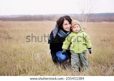 Adorable young mother hugging her child boy during walk in the park on beauty winter day - stock photo
