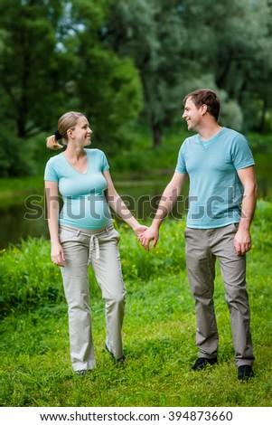 Adorable young pregnant woman and happy handsome man smiling, holding each other hands and looking at each other in summer park. Happy family and pregnancy concept. Mother's Day - stock photo