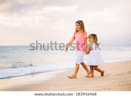 Adorable Young Sisters, Two Little Girls Walking together on the Beach at Sunset, Family Lifestyle. - stock photo