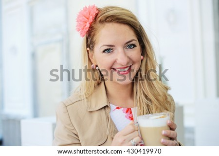 Adorable young woman with cup of coffee in the city cafe