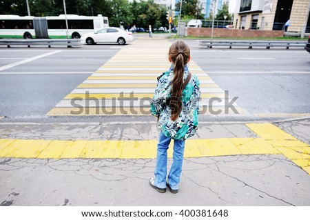 Adorableschool aged kid girl in glasses and fashion  clothes standing  near the pedestrian crossing on the city street - stock photo