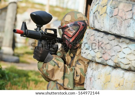 Adrenalin paintball player in protective uniform and mask aiming gun before shooting in summer - stock photo