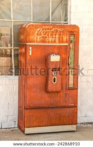 ADRIAN, TEXAS - AUGUST 25, 2013:  Photo of an old, rusty Coca-Cola vending machine manufactured by Vendo and telling us to Drink Coca-Cola in Bottles at ten cents each - stock photo