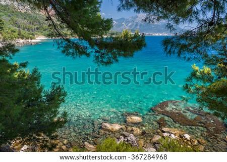 Adriatic sea bay view through the frame of green tree branches. Montenegro. - stock photo