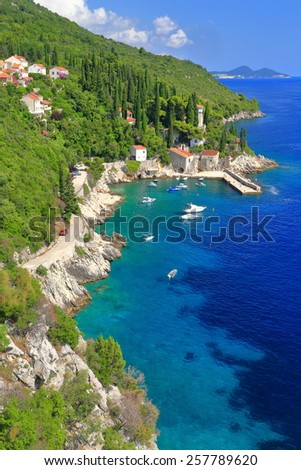Adriatic sea coastline with small harbor and boats surrounded by green hills, Trsteno, Croatia - stock photo