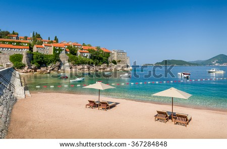 Adriatic sea luxury sand beach with chaise-longue chairs and umbrellas near the Sveti Stefan historical town on a small island. Montenegro. - stock photo